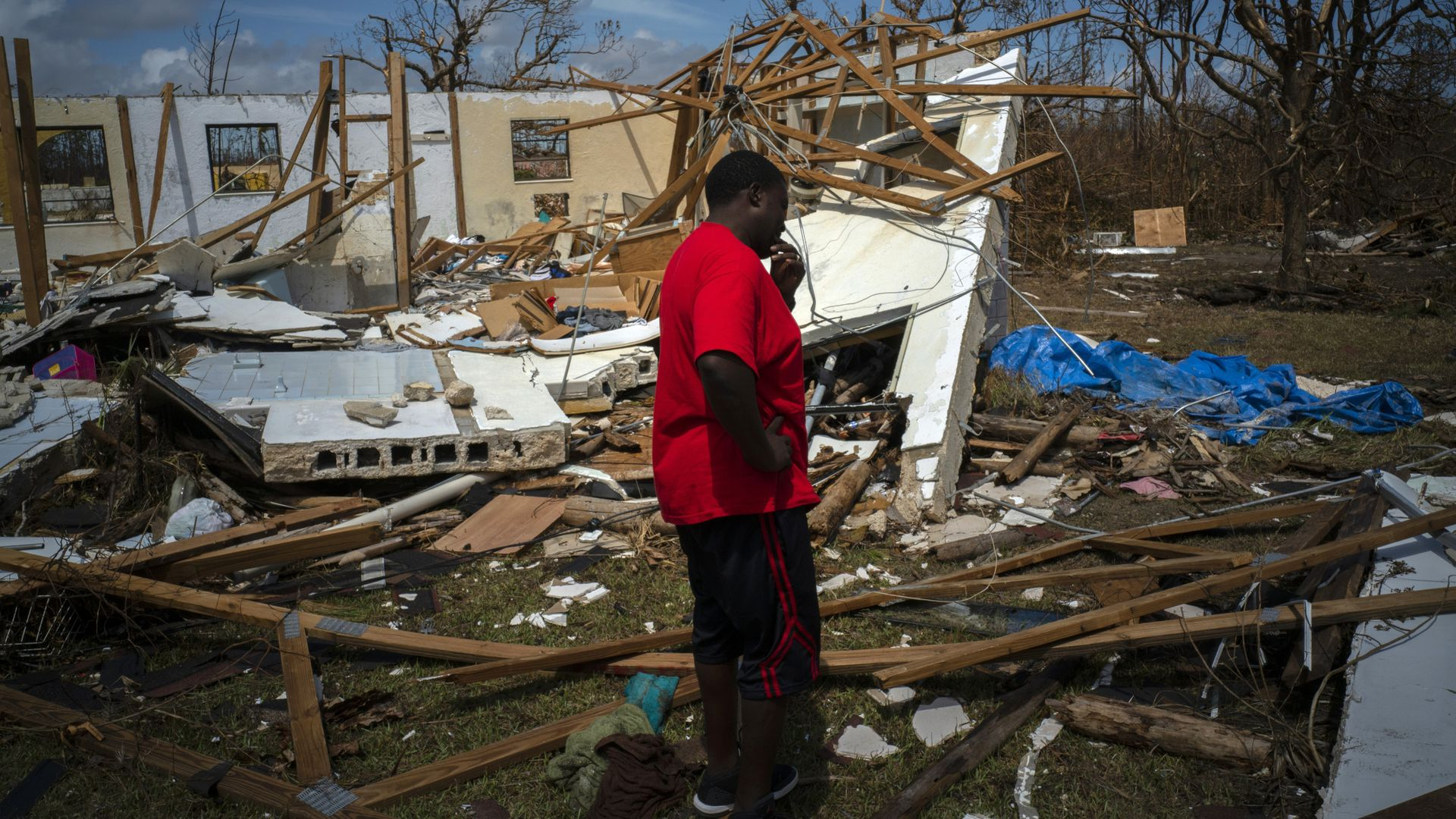 A man cries at the sight of his destroyed house in the Bahamas