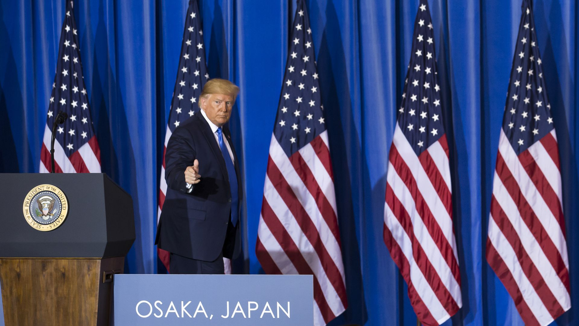 President Trump on stage after a press conference in Japan.