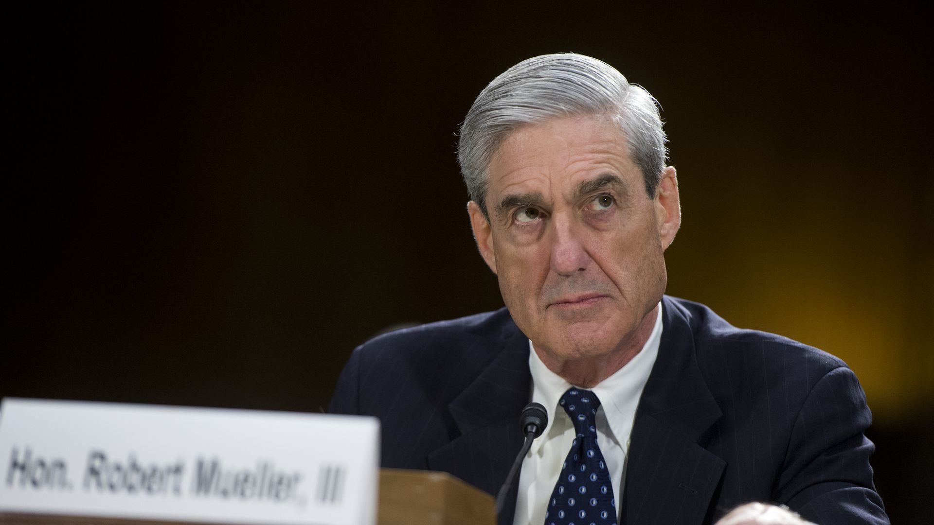 Mueller sits at desk looking stern.
