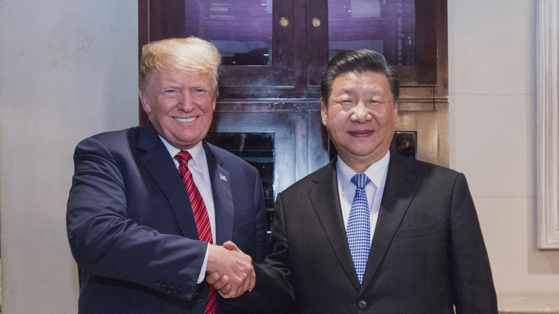 President Trump and Chinese President Xi Jinping smile while shaking hands