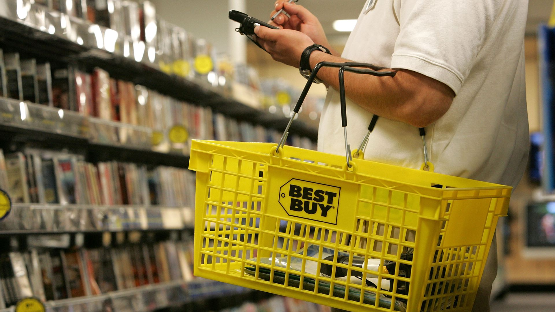 A salesman carries a Best Buy shopping basket.