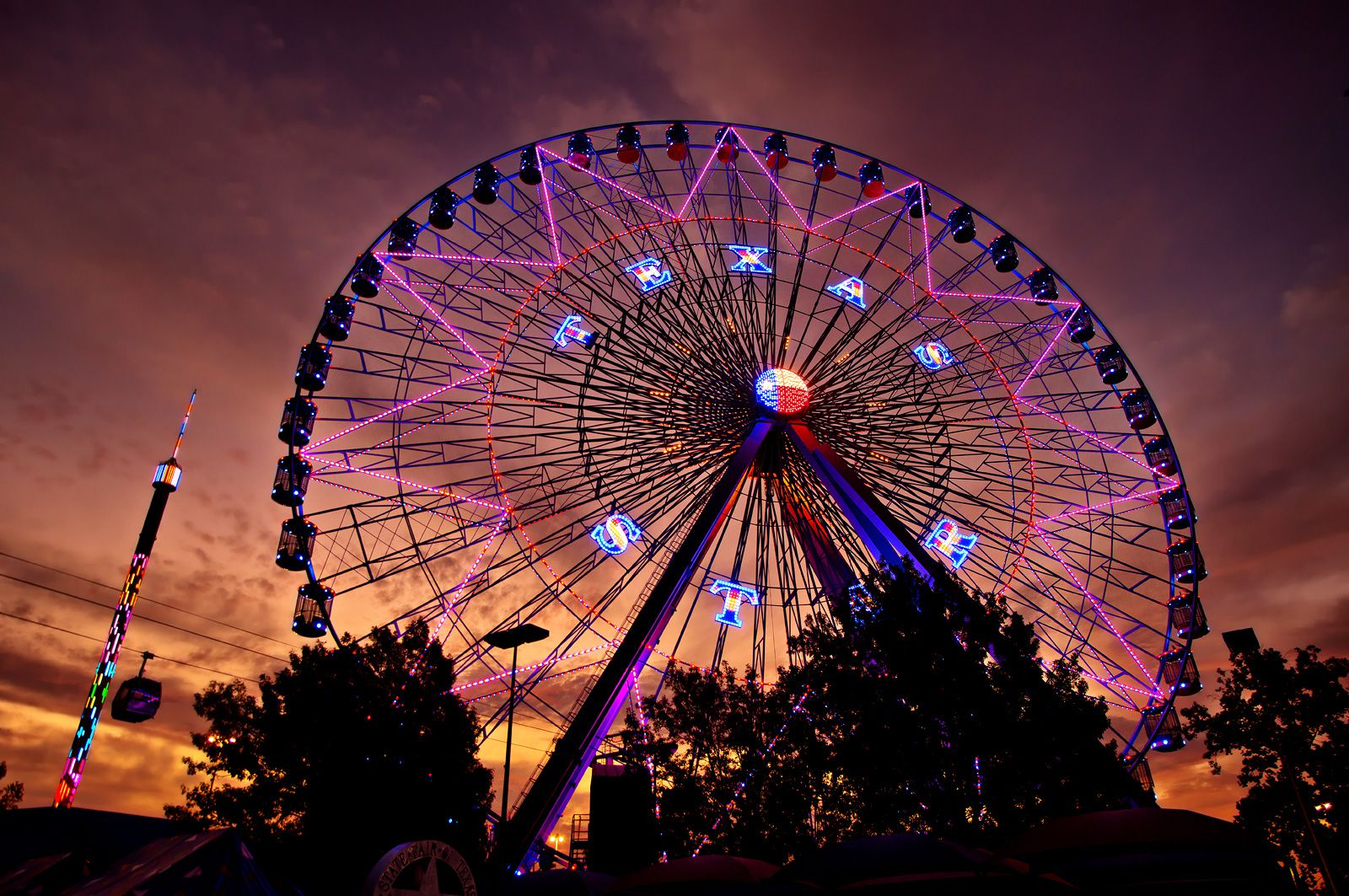 The Texas Star Ferris Wheel lit up in neon against a technicolor sunset.