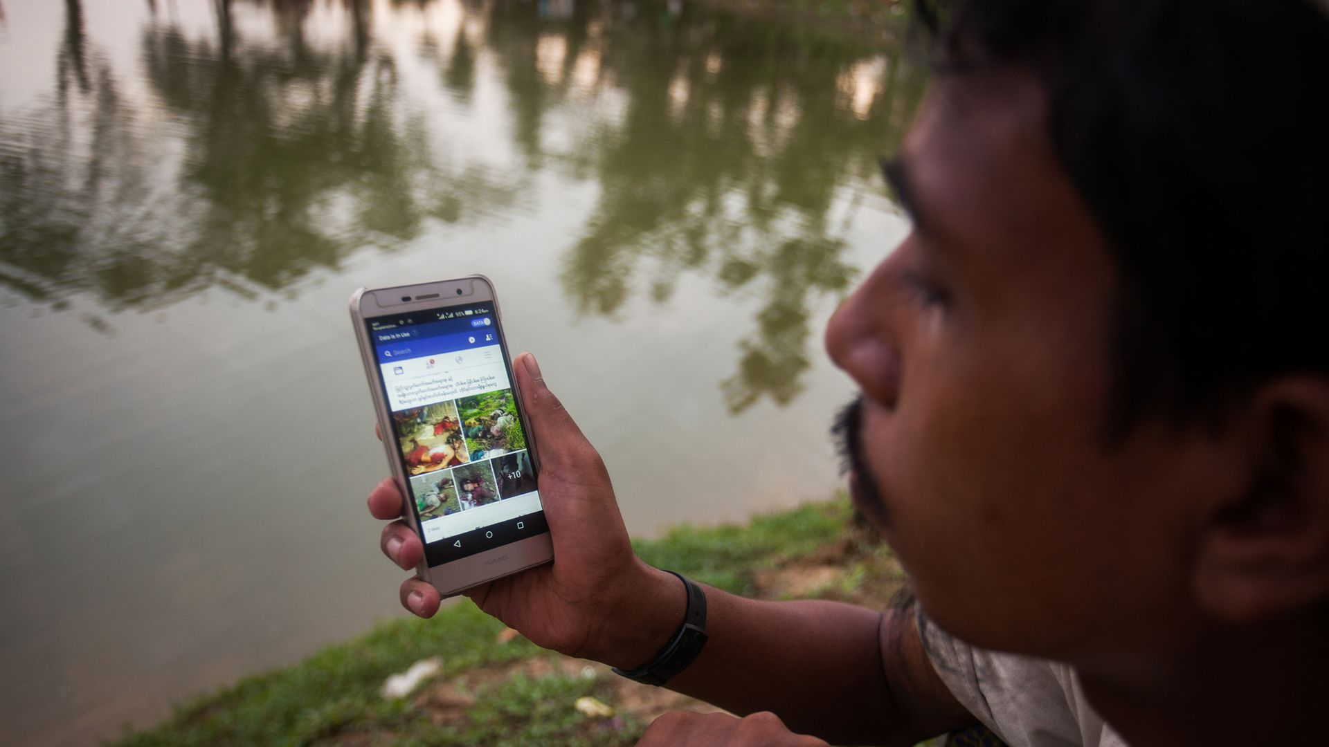 Rohingya man looking at Facebook on his phone