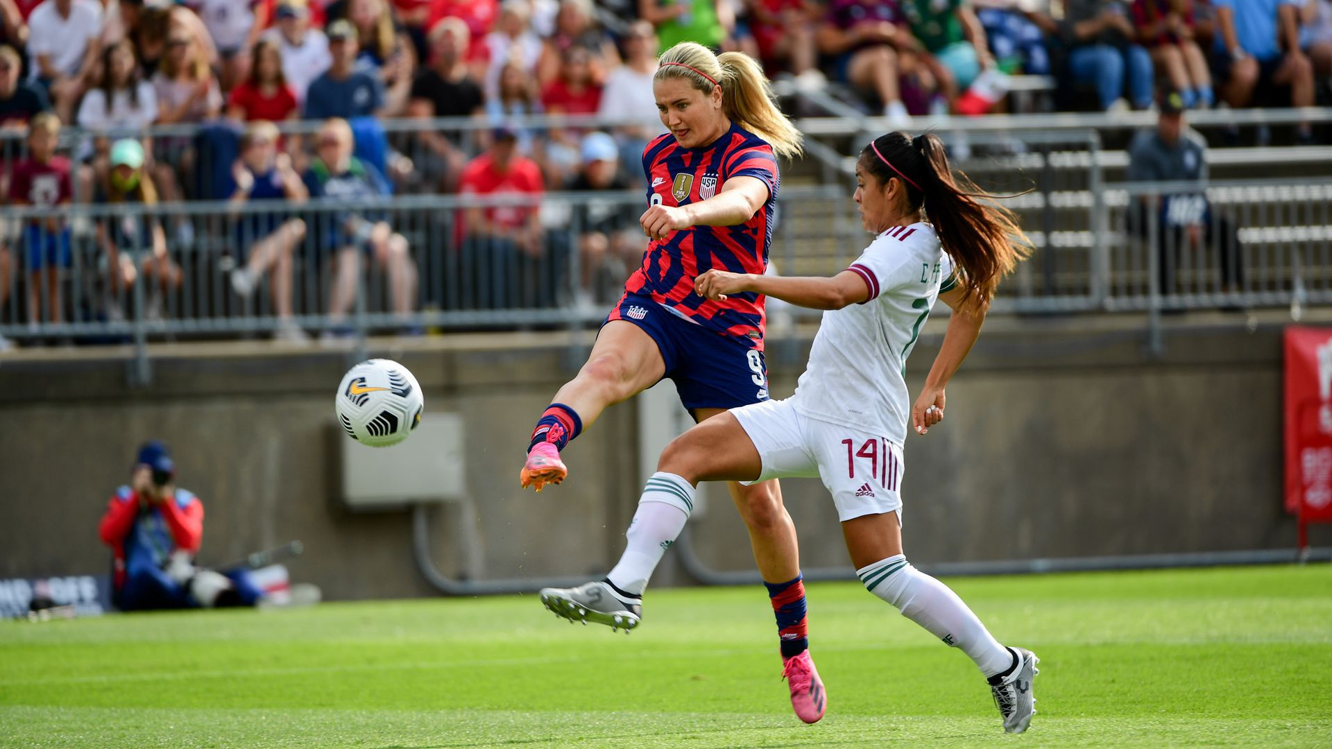 Lindsey Horan kicks the soccer ball during a game.