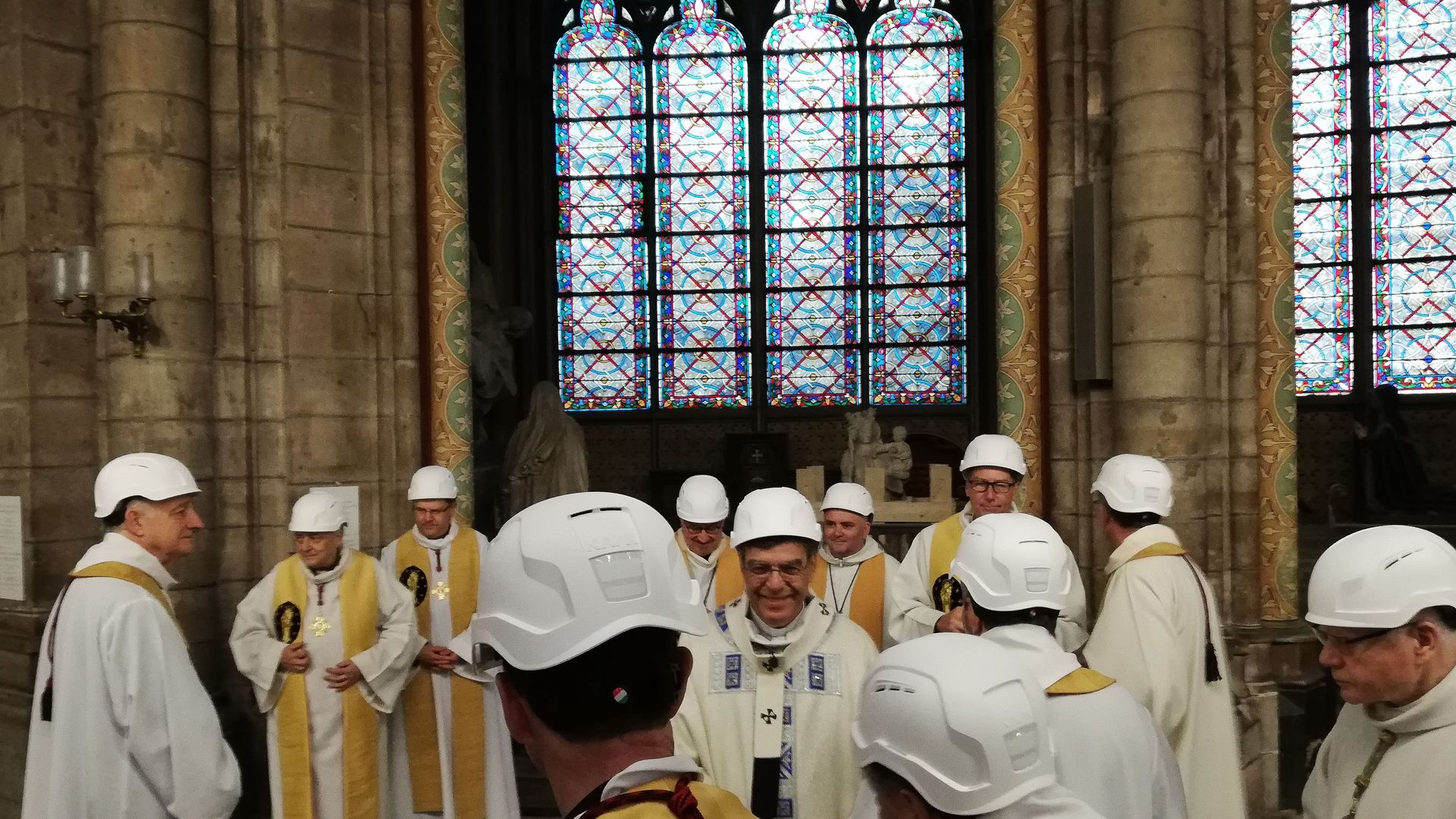 The Archbishop of Paris Michel Aupetit (C) greets other clergy following the first mass in a side chapel, after a fire engulfed the Notre-Dame de Paris cathedral, on June 15, 2019, in Paris.