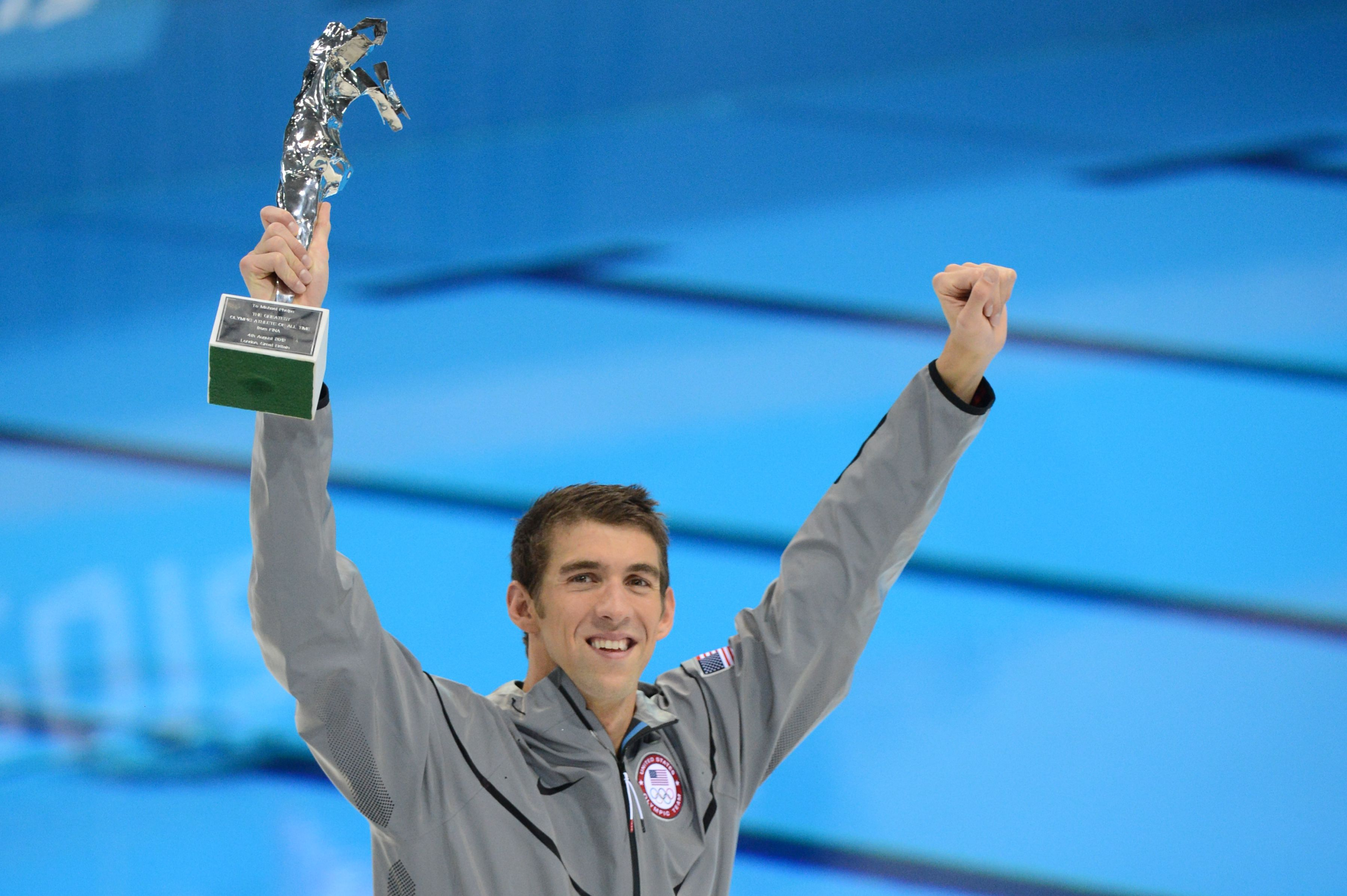 Michael Phelps holds up trophy