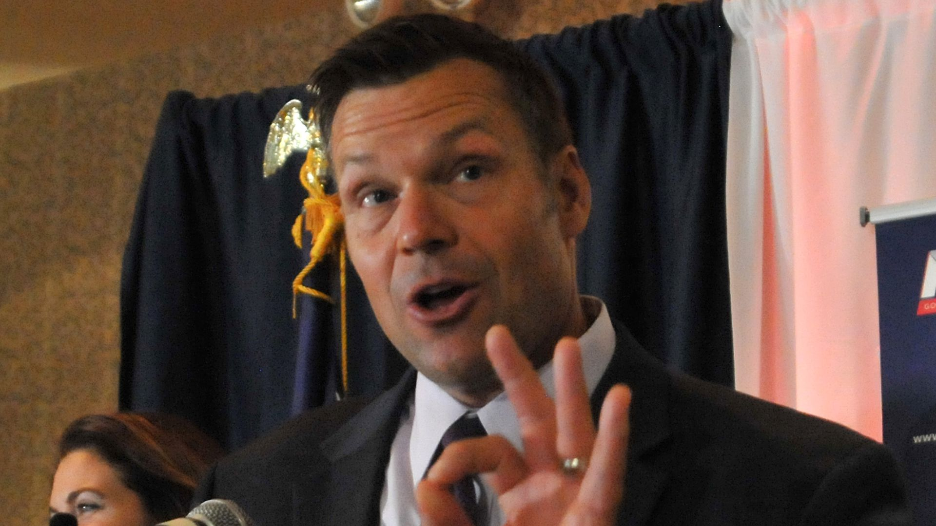 """Kris Kobach speaking at a microphone holding up the """"okay"""" sign with his left hand"""