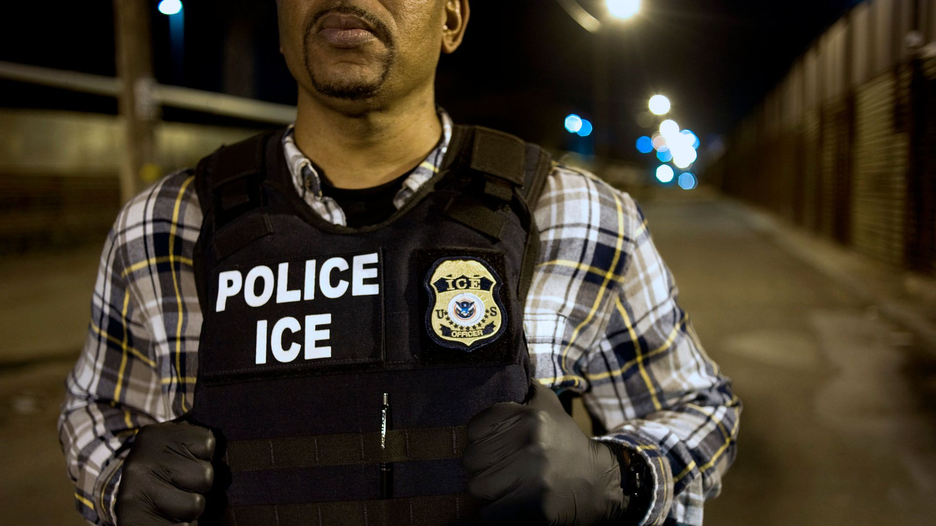 In this image, an ICE officer holds onto his vest as he stands in the street at night.