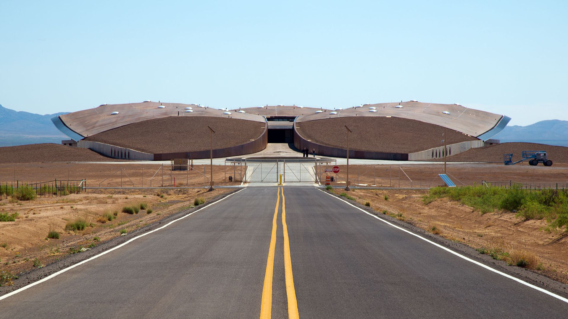 In this image, Spaceport America is seen at the end of a long desert road. It looks like a large drone.