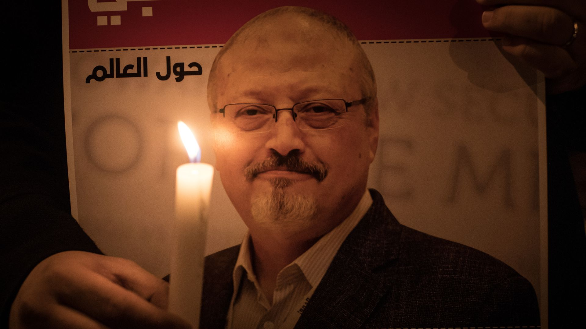 Jamal Khashoggi portrait next to candlelight at vigil.