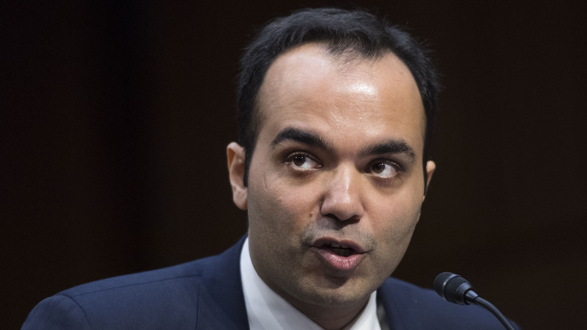 FTC Commissioner Rohit Chopra speaks at a microphone, wearing a suit and tie