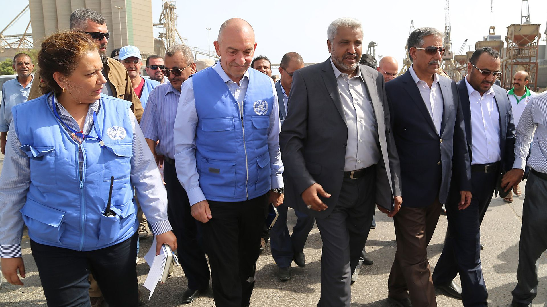 UN peacekeepers and acting governor of Hodeidah walking near port