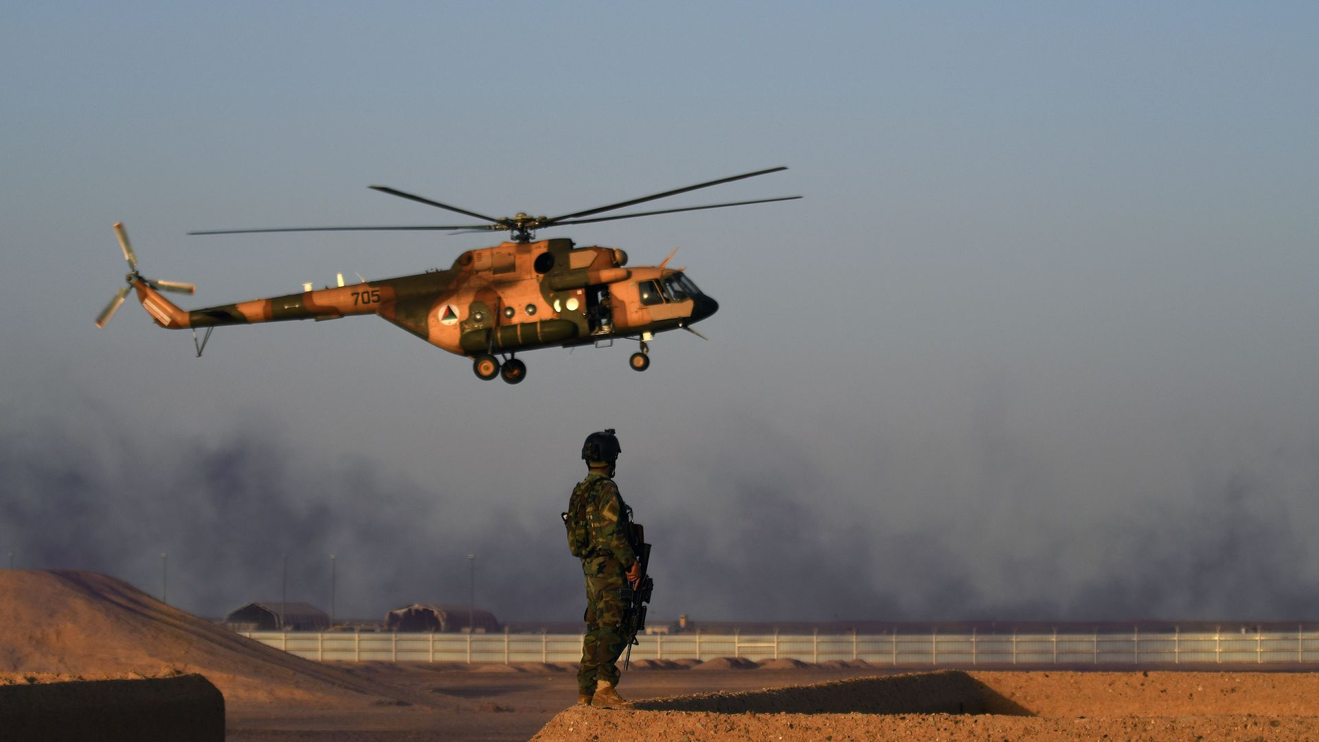 An Afghan Commando stands guard while a helicopter flies past next to Kabul's airport