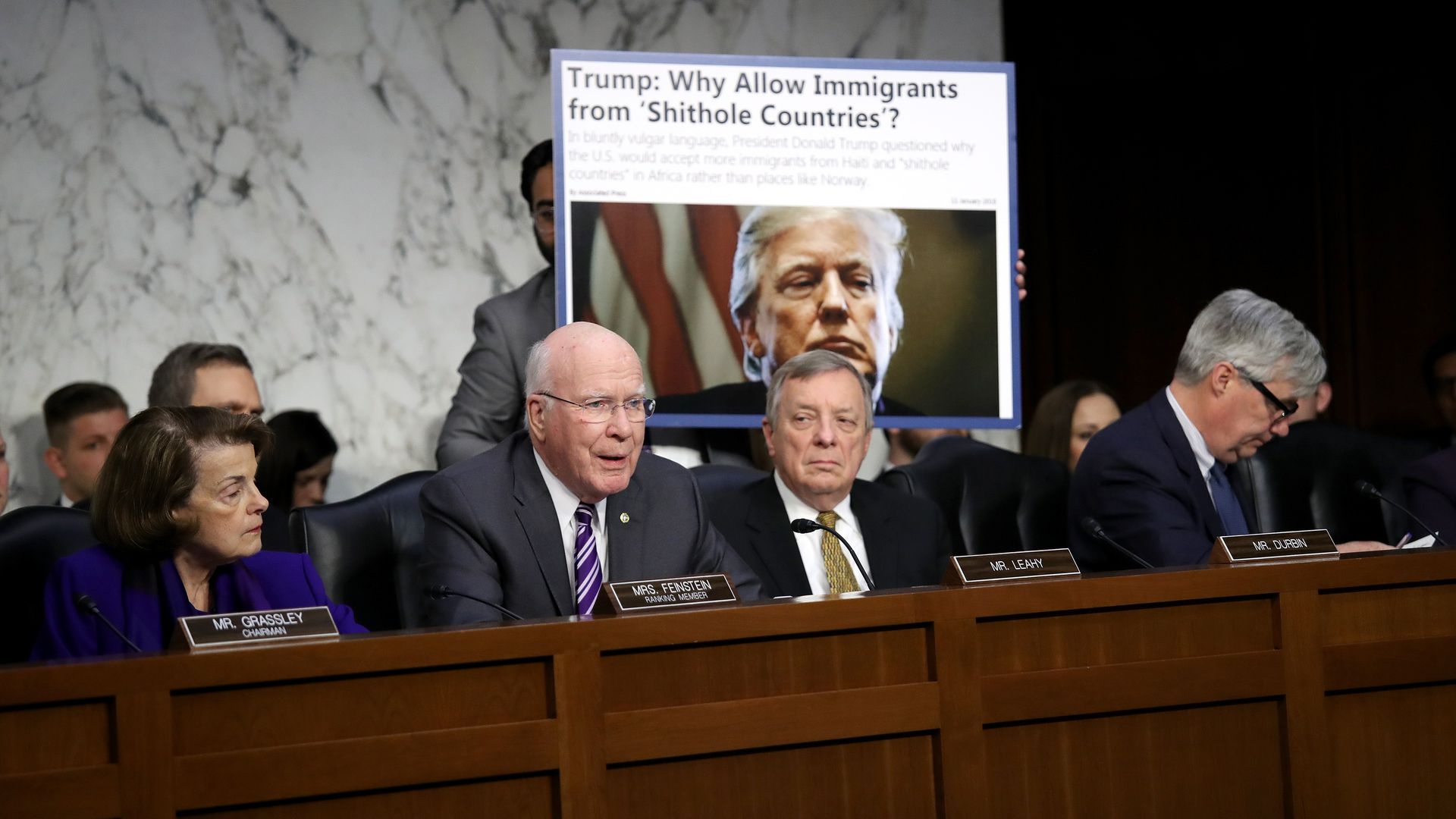 The Senate Judiciary Committee confers with an aide holding up a screenshot of a headline with Trump's vulgar language