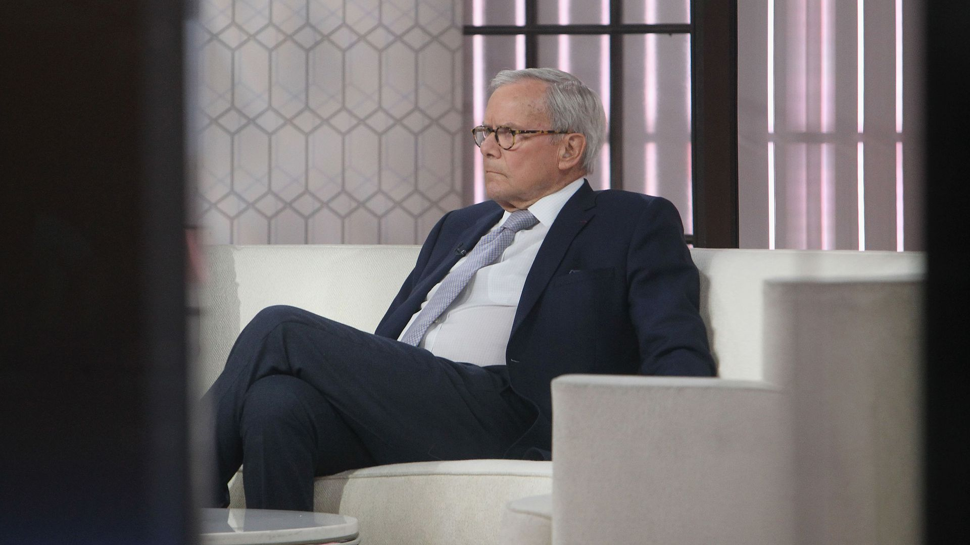 Tom Brokaw sitting on a couch.