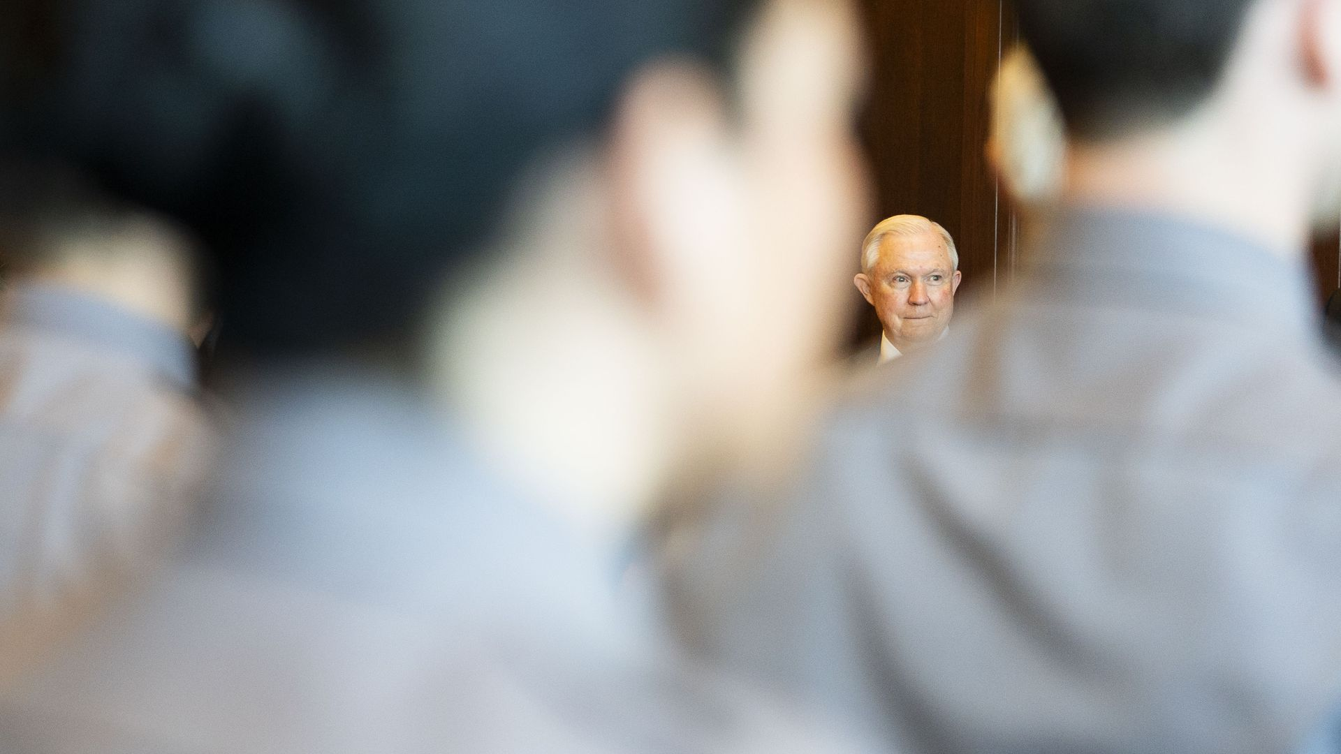 Jeff Sessions seen through a blurry foreground of men wearing grey shirts