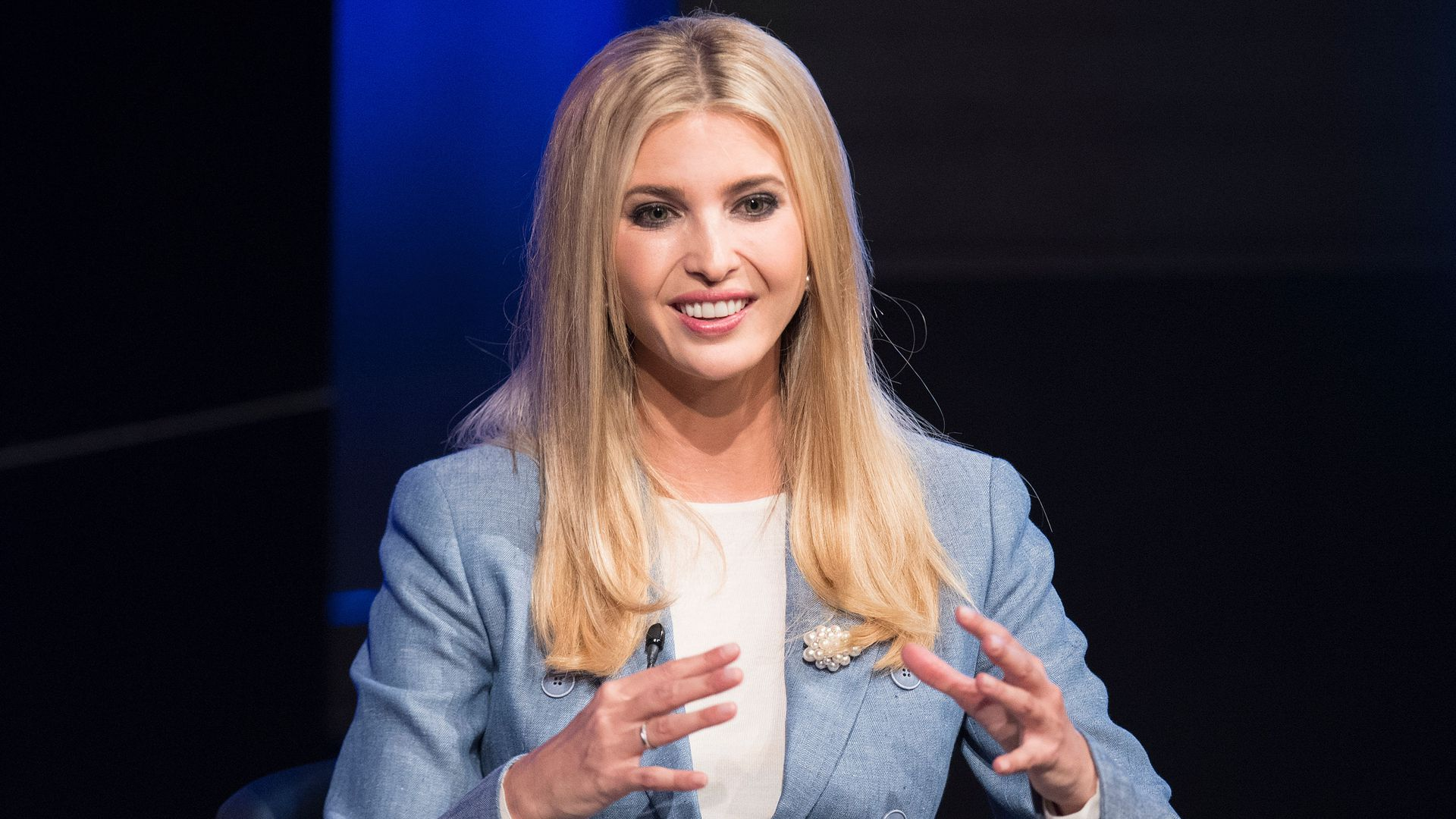 Ivanka Trump speaks enthusiastically with her hands on stage at an Axios event