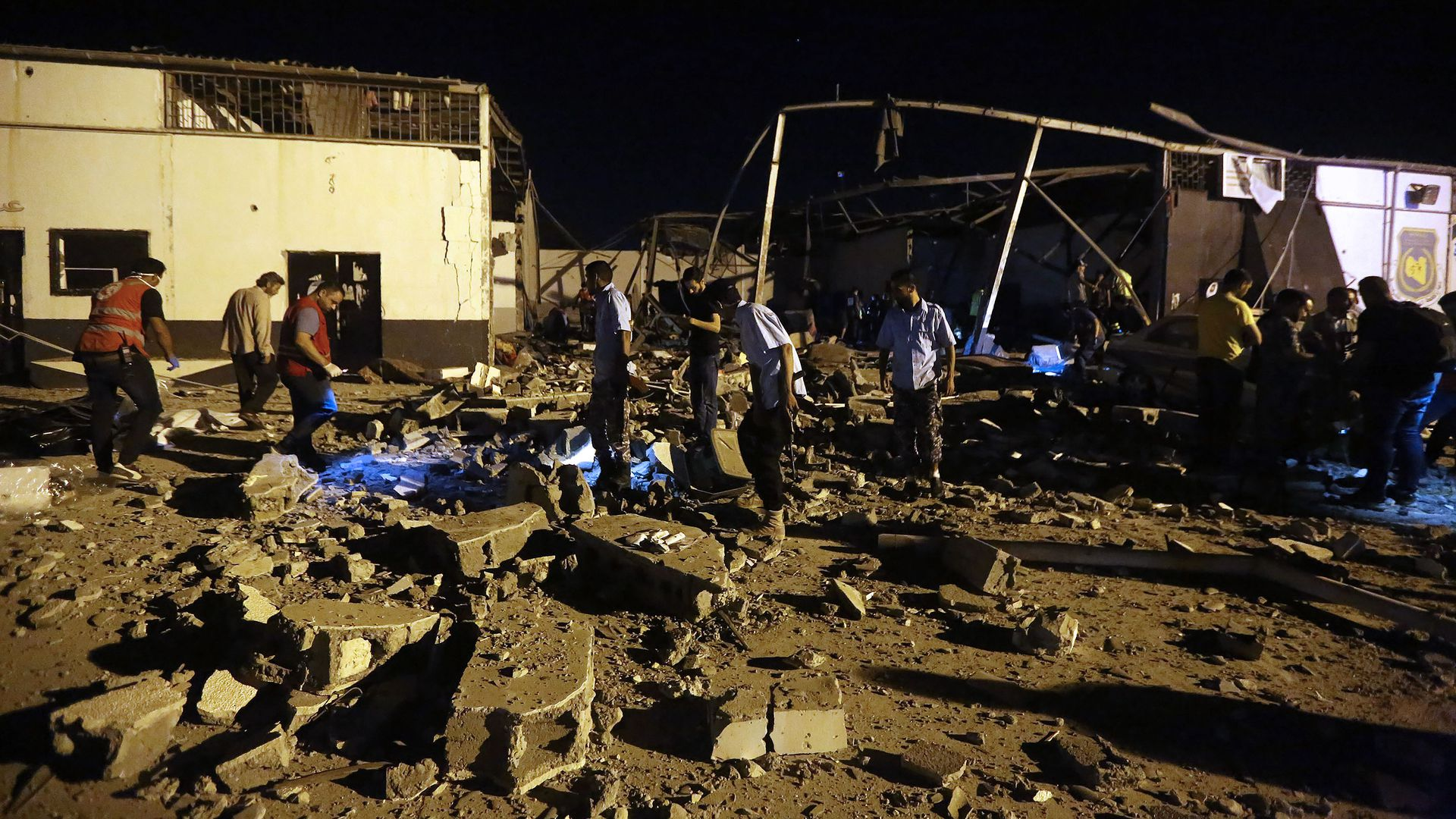 Emergency workers and other recover bodies after an airstrike killed nearly 40 at Tajoura Detention Center, east of Tripoli.