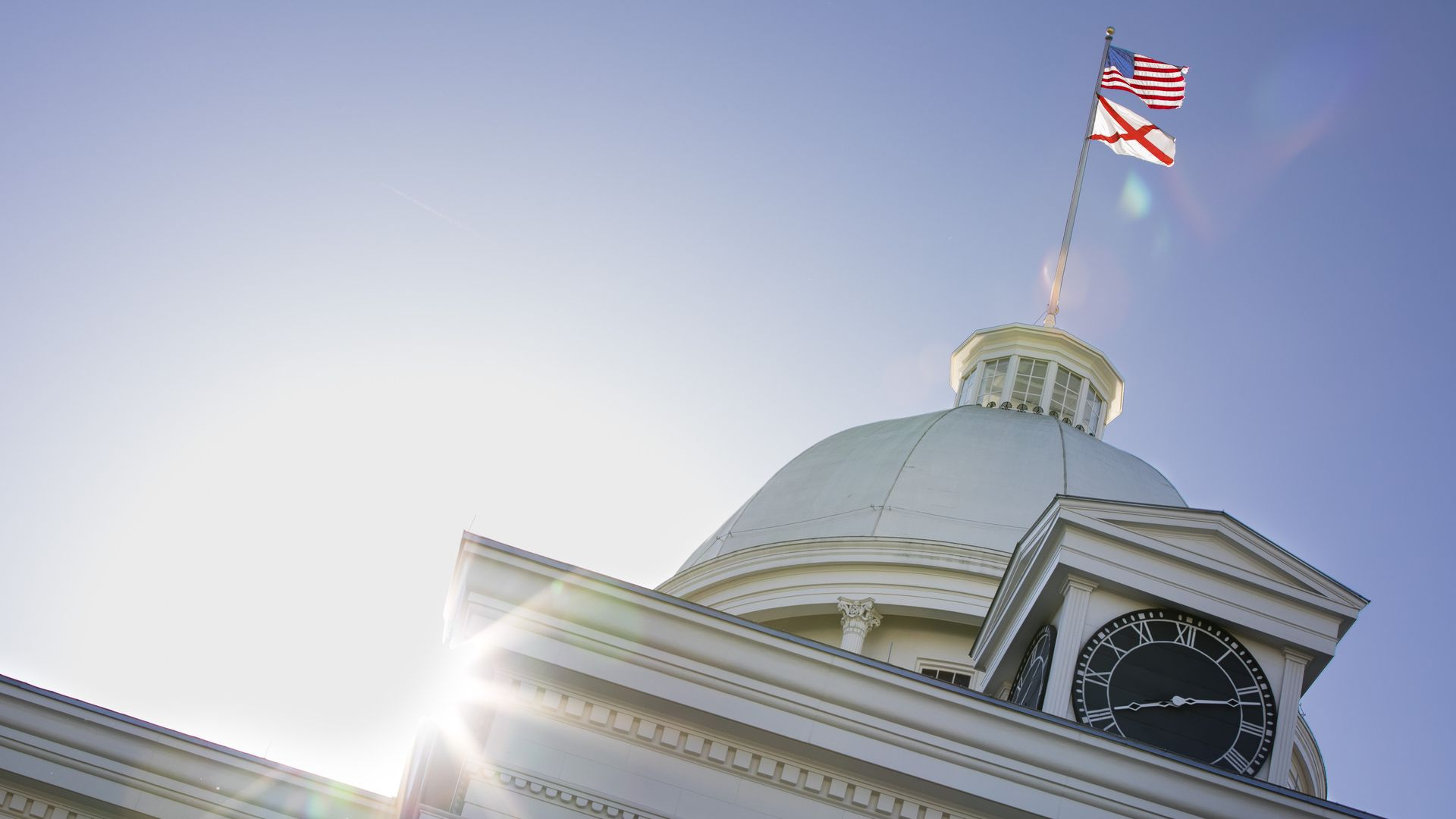 The flag of Alabama below the U.S. flag fly over a Montgomery Statehouse.