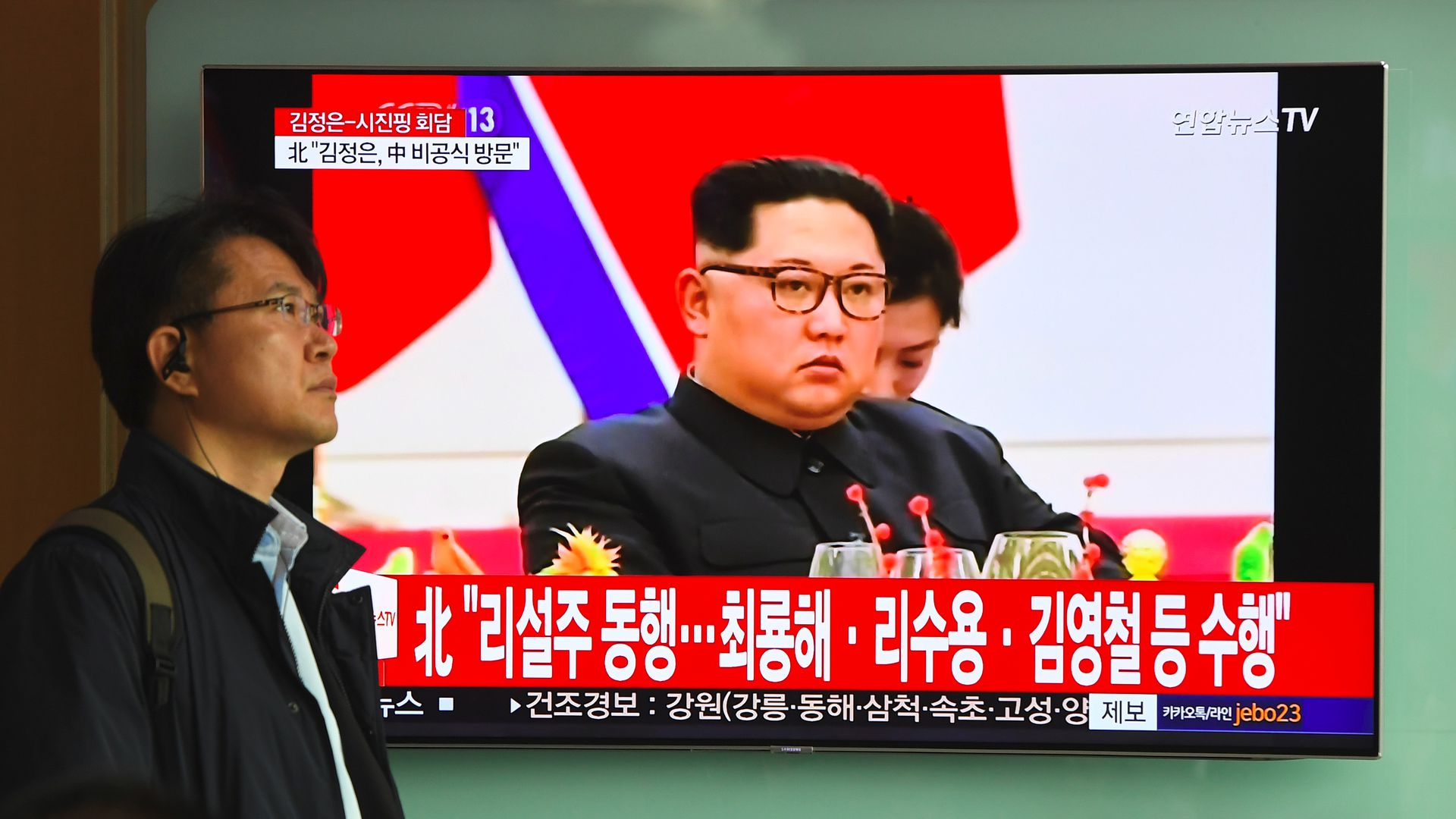 Kim Jong-un displayed on a TV with a red backdrop.