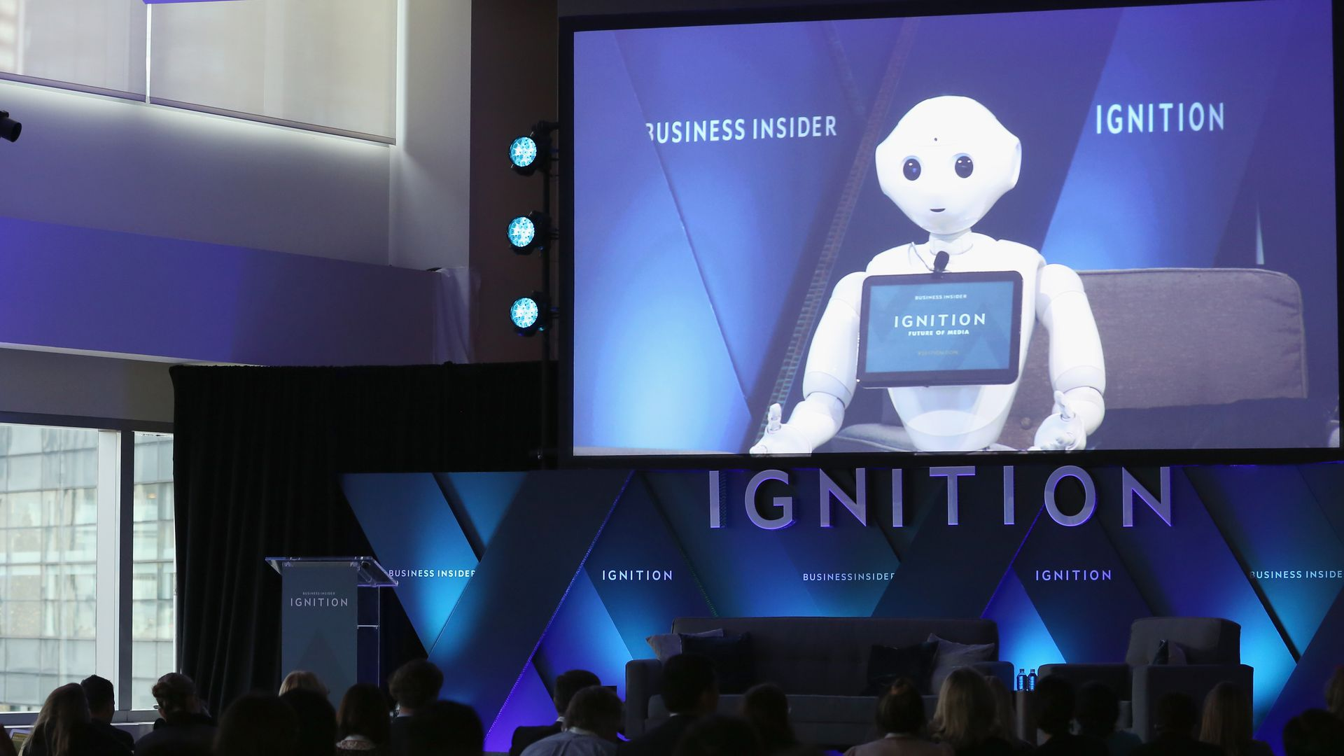 A robot is shown on a screen at a conference
