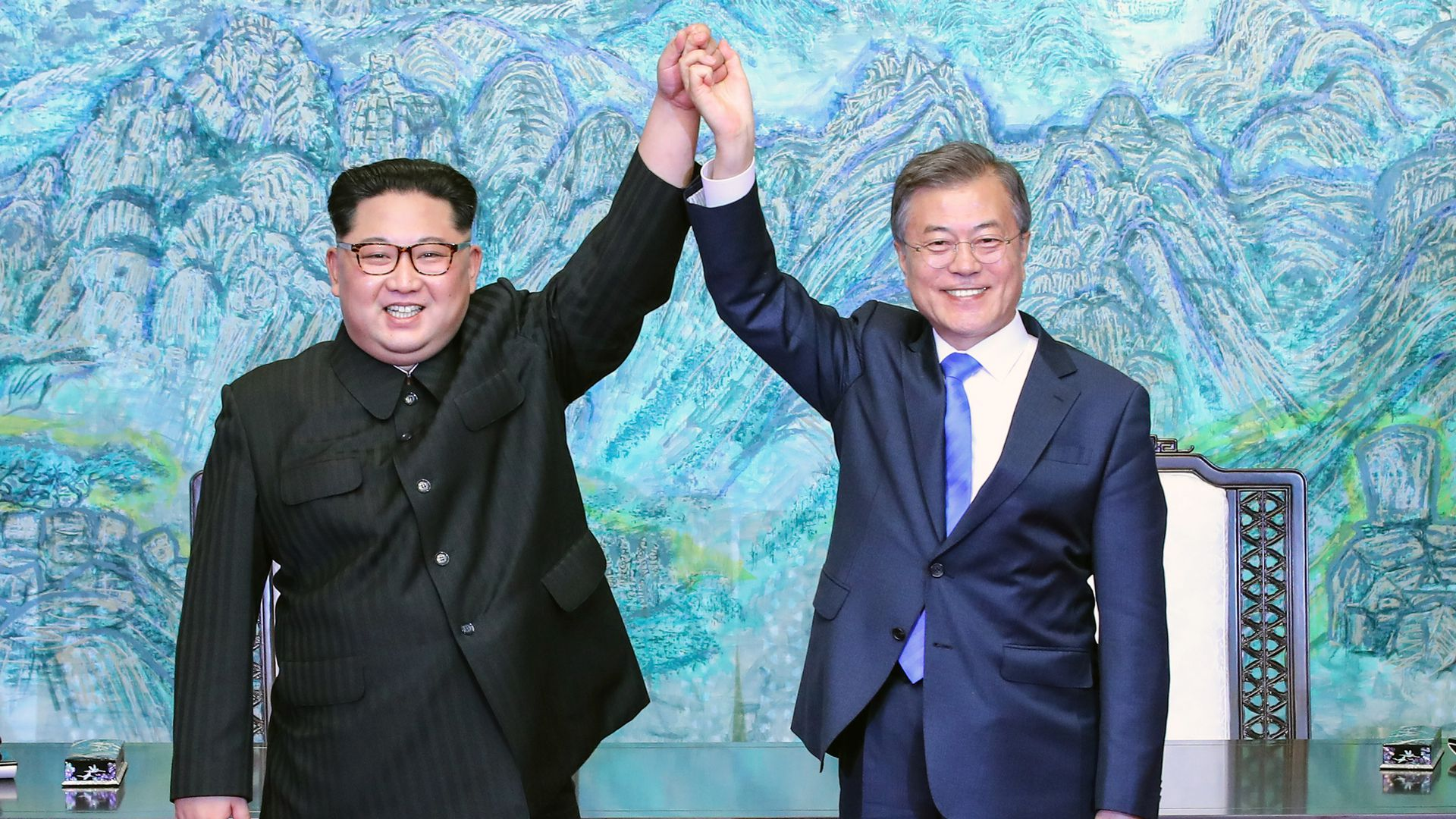 Kim Jong-un and Moon Jae-in holding hands at their summit