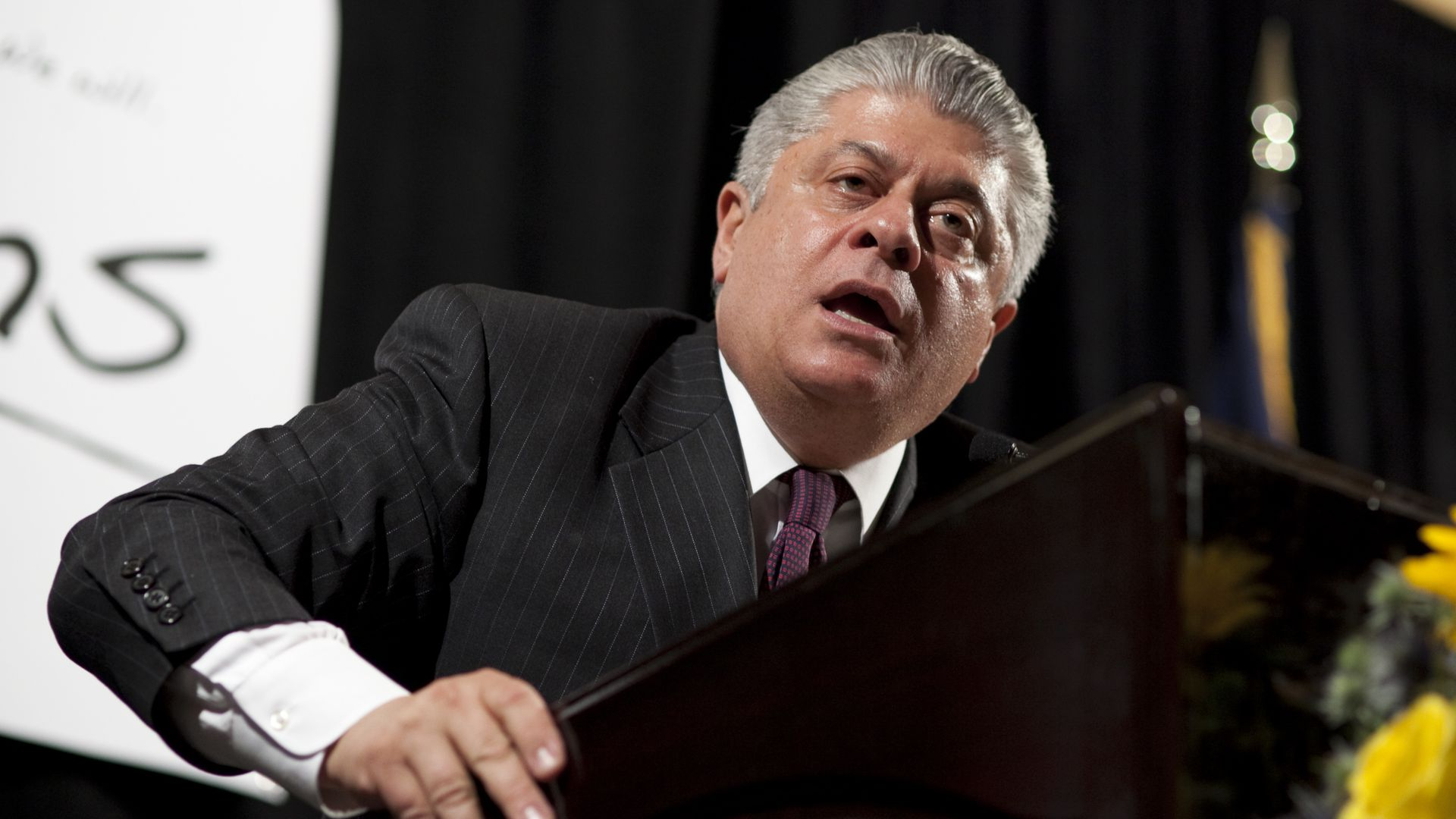 In this image, Andrew Napolitano leans over a podium and speaks at a crowd.