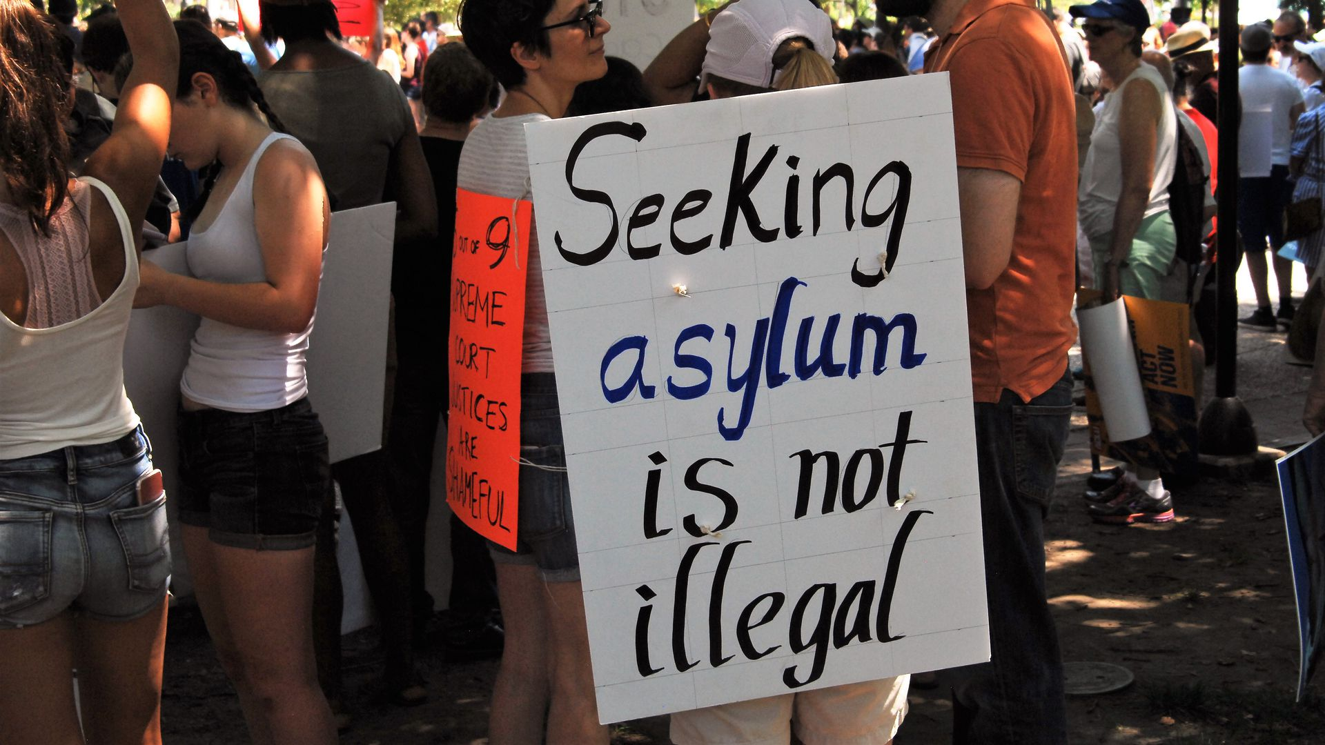 "Protestors with one holding a sign that says ""Seeking asylum is not illegal"""