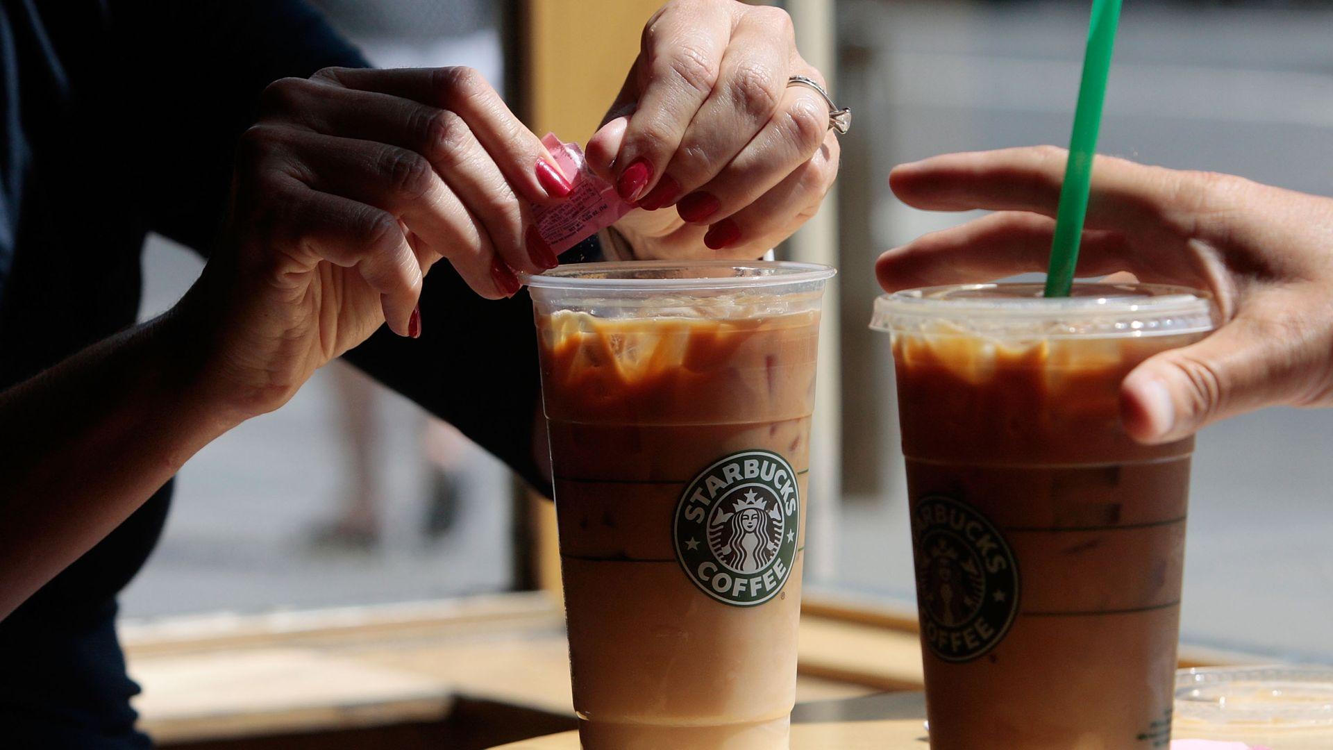 Two people prepare cold Starbucks drinks
