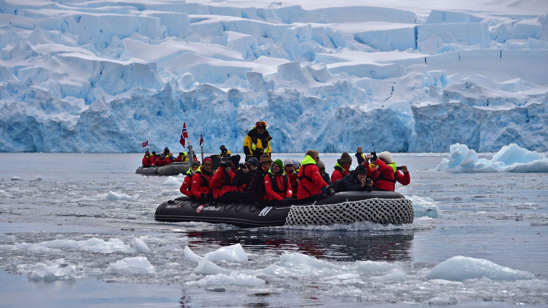 In this image, a large group of people sit in a boat on ice water in the Antarctic