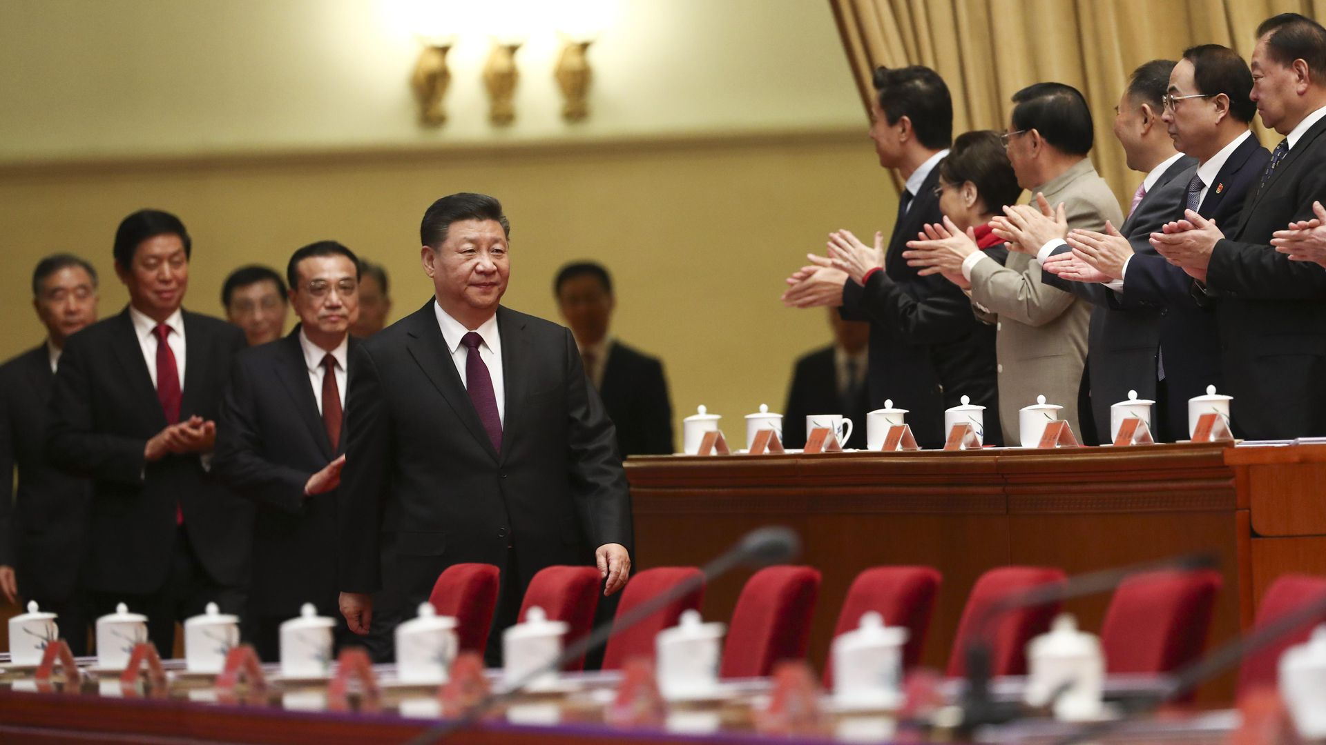 Chinese President Xi Jinping walking through his party headquarters with people clapping