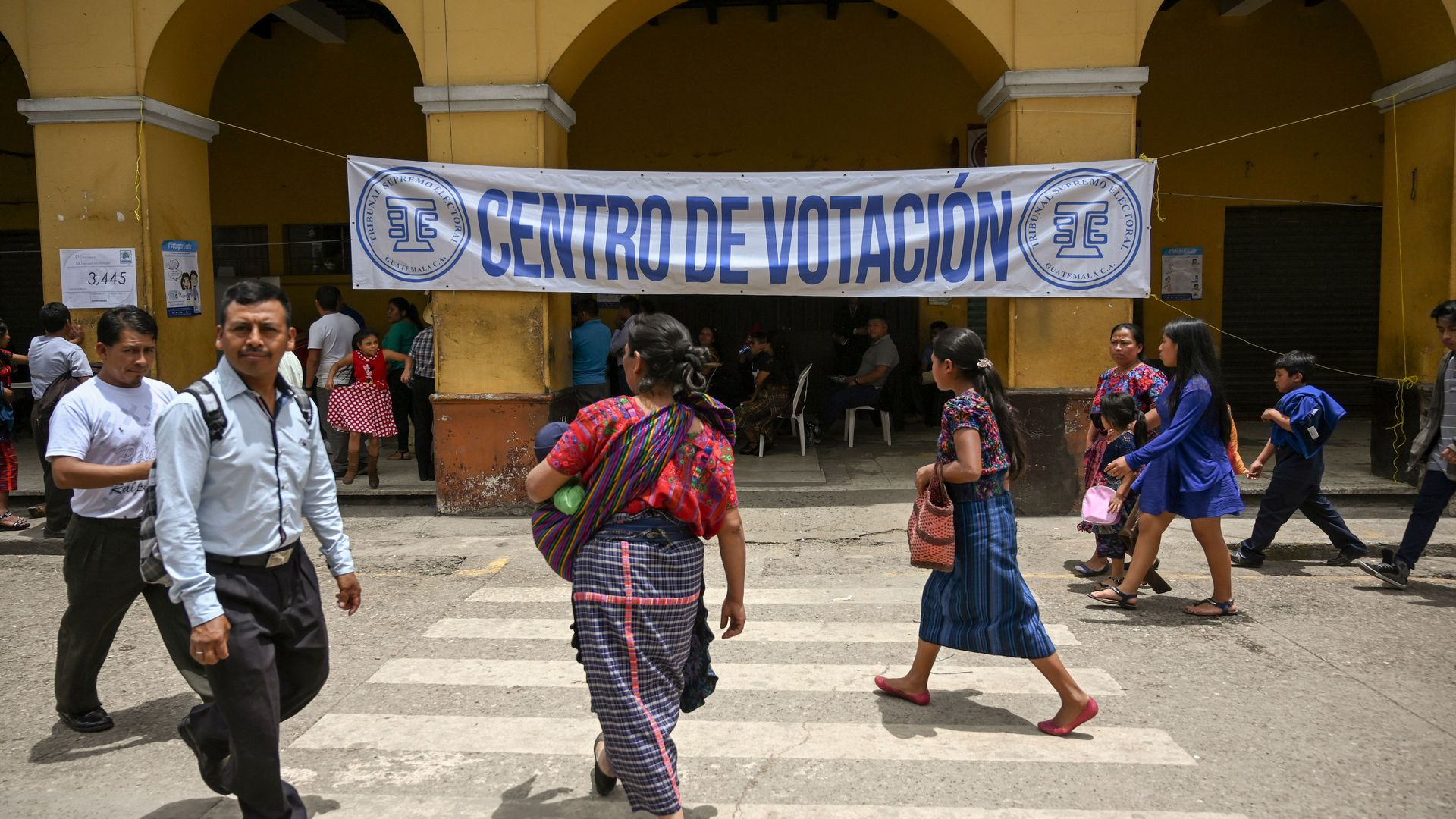 Guatemalans walking outside a polling center
