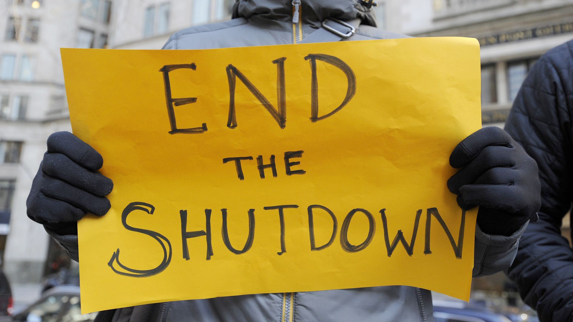 "Sign reads ""END THE SHUTDOWN."""