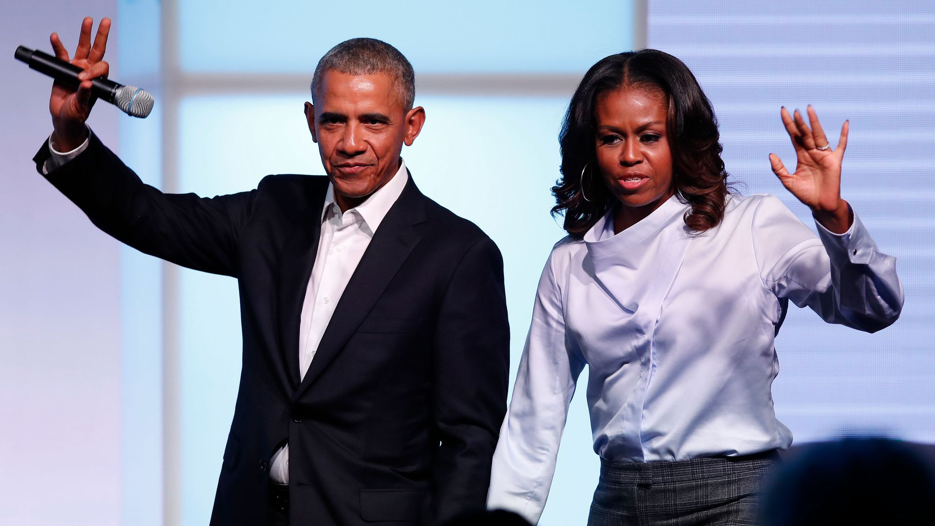 Barack and Michelle Obama wave to the crowd at the Obama Foundation Summit.