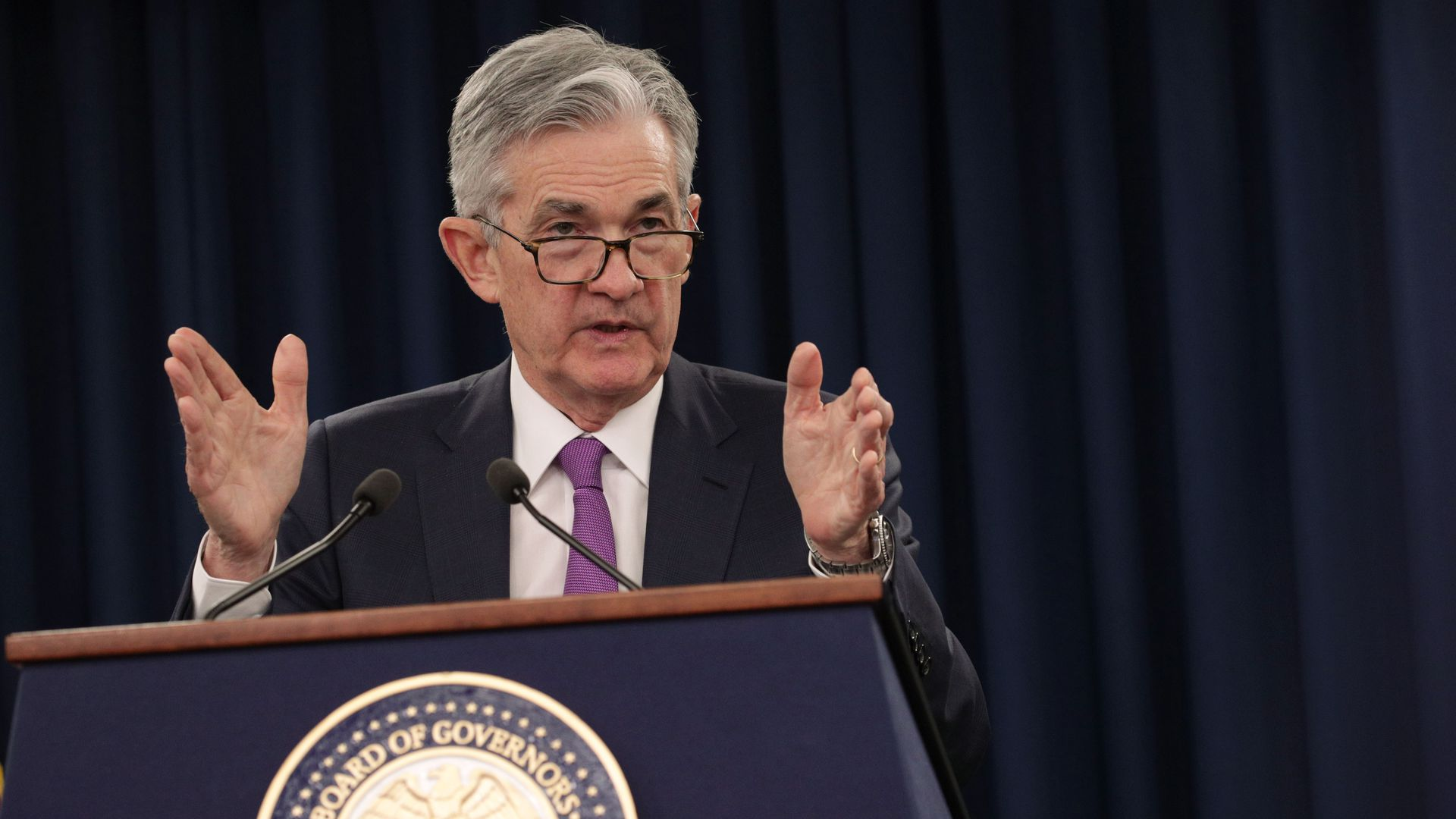 In this image, Federal Reserve Board Chairman Jerome Powell speaks into two microphones from behind a podium.